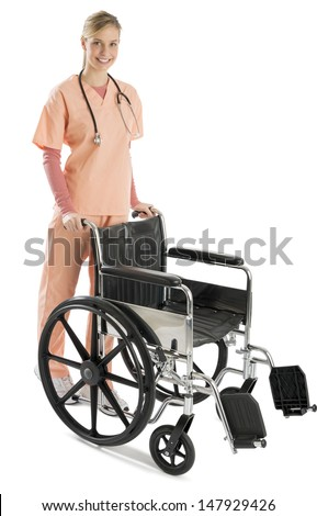 Full length portrait of beautiful female nurse with wheelchair standing isolated over white background - stock photo