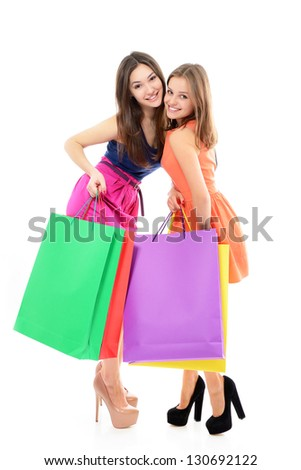 full length portrait of beautiful happy teen girls with colored shopping sale bags over white - stock photo