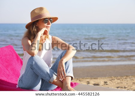 Full length portrait of beautiful mature woman relaxing on the sandy beach while sitting on the sunbed. - stock photo
