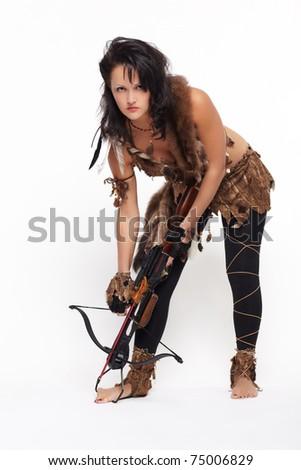 full-length portrait of beautiful woman fur hunter reloading crossbow on gray - stock photo
