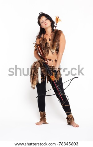 full-length portrait of beautiful woman fur hunter with crossbow on gray - stock photo