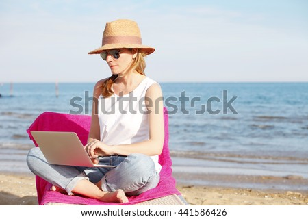 Full length portrait of beautiful woman with laptop working on the beach.