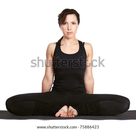 full-length portrait of beautiful woman working out yoga excercise baddha konasana (bound angle pose) on fitness mat - stock photo