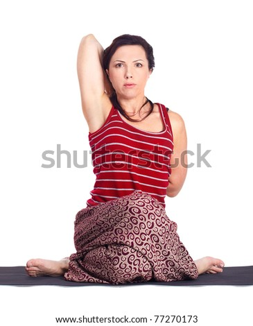 full-length portrait of beautiful woman working out yoga excercise gomukhasana (cow face pose) on fitness mat - stock photo