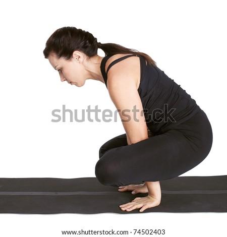 full-length portrait of beautiful woman working out yoga excercise kukkutasana on fitness mat - stock photo
