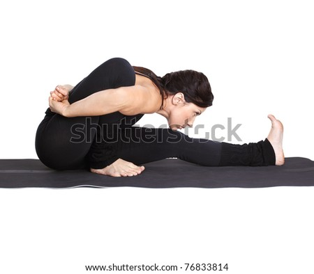 full-length portrait of beautiful woman working out yoga excercises Marichiasana pose on fitness mat - stock photo
