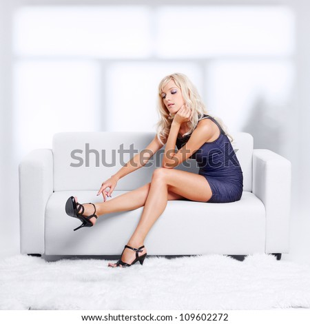 full-length portrait of beautiful young blond woman on couch streching legs in court shoes