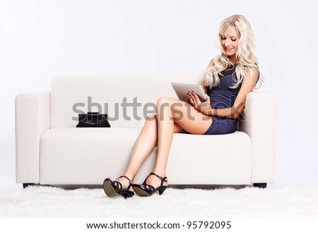 full-length portrait of beautiful young blond woman on couch with tablet pc