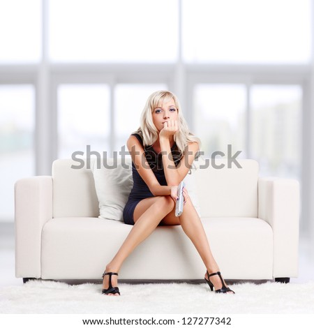 full-length portrait of beautiful young blond woman sitting on couch with remote control - stock photo