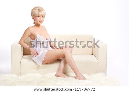 full-length portrait of beautiful young blonde woman in lingerie on white coach