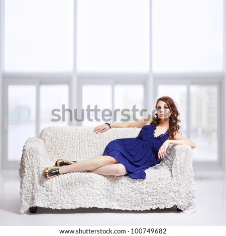 full-length portrait of beautiful young brunette woman in blue dress and jewelry relaxing on sofa with large windows on background - stock photo