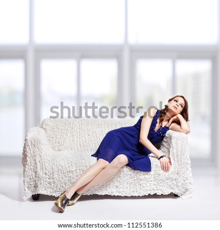full-length portrait of beautiful young brunette woman in blue dress, jewellery and court shoes relaxing on sofa