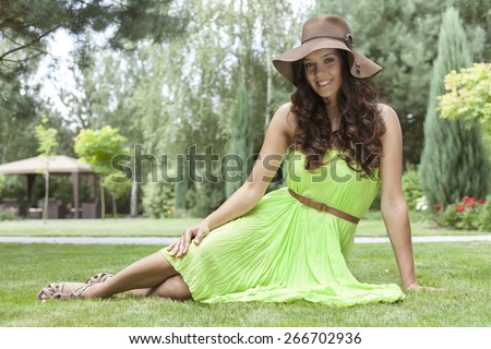 Full length portrait of beautiful young woman in sundress at park - stock photo