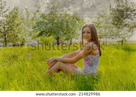 Full length portrait of beautiful young woman lying on a meadow against white flower on apple tree Cute slim girl in gray dress looking up and enjoying Empty Copy space for inscription - stock photo