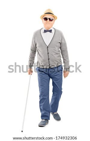 Full length portrait of blind senior gentleman walking with a stick isolated on white background - stock photo