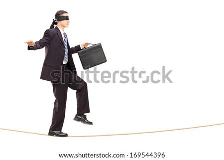 Full length portrait of blindfolded young businessman walking on rope, isolated on white background - stock photo