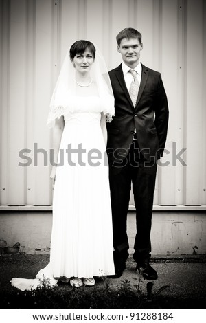 Full length portrait of bride and groom standing against wall - stock photo