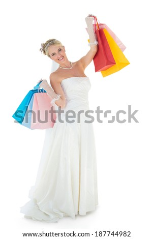 Full length portrait of bride carrying shopping bags over white background