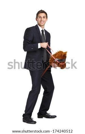 Full-length portrait of businessman riding the toy horse, isolated on white - stock photo