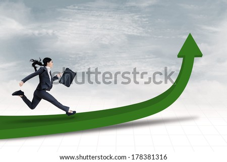 Full length portrait of businesswoman with briefcase running on arrow up - stock photo