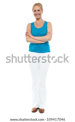 Full length portrait of casual cheerful woman posing with arms folded over white background - stock photo