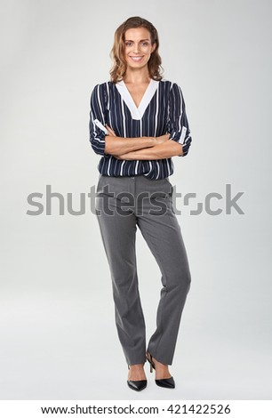 Full length portrait of caucasian business woman in studio, isolated on grey - stock photo