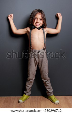 full length portrait of cheerful cute little boy posing and smiling on dark grey background - stock photo