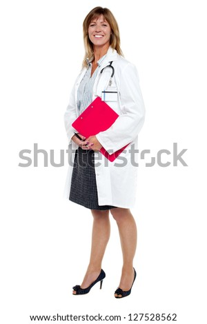 Full length portrait of cheerful female physician with clipboard and pen. - stock photo