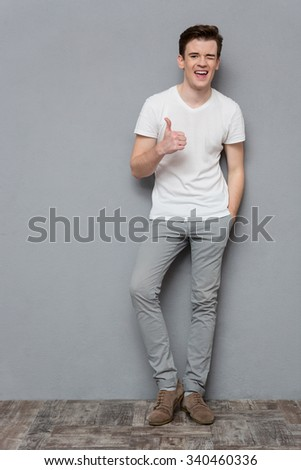 Full length portrait of cheerful handsome inspired confident young man in white t-shirt and gray pants showing thumbs up and winking on gray background - stock photo