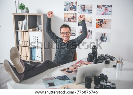 Full length portrait of cheerful unshaven photographer relaxing on chair near desk with camera, laptop and pictures. He flourishing arms. Relax concept