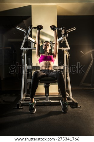 Full length portrait of Cheerful young adult caucasian woman working out on exercise machine inside gym dark room background Empty space for inscription Dramatic light in dusk  - stock photo
