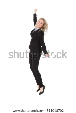 Full length portrait of cheerful young businesswoman jumping against white background - stock photo