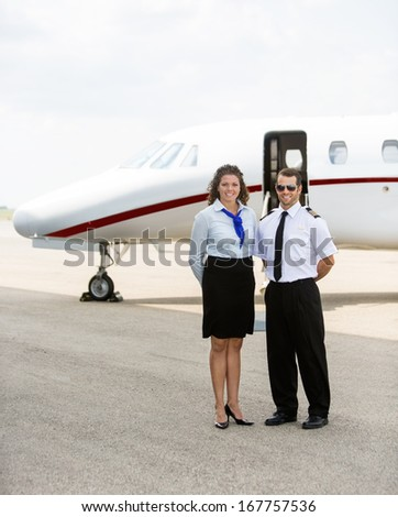 Full length portrait of confident airhostess and pilot standing together against private jet - stock photo