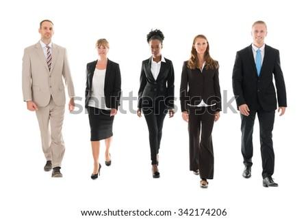 Full length portrait of confident business team walking against white background - stock photo