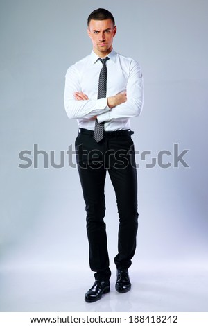 Full-length portrait of confident businessman with arms folded on gray background - stock photo