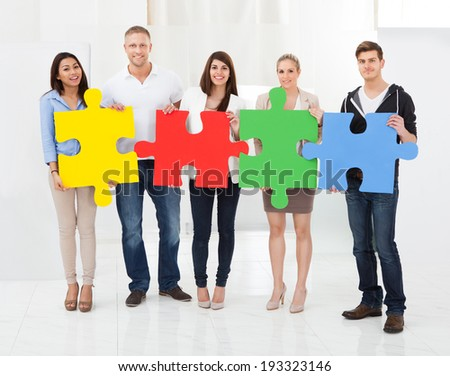 Full length portrait of confident businesspeople joining puzzle pieces in office - stock photo
