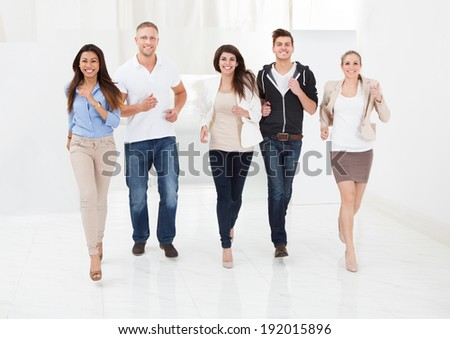 Full length portrait of confident businesspeople running together in office - stock photo