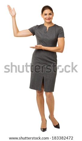 Full length portrait of confident businesswoman presenting an imaginary product over white background. Vertical shot. - stock photo