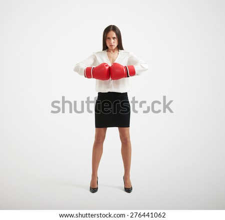 full length portrait of confident businesswoman with red gloves looking at camera over light background - stock photo