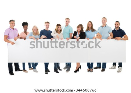 Full length portrait of confident creative business team holding blank billboard against white background - stock photo
