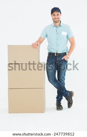 Full length portrait of confident delivery man with cardboard boxes on white background - stock photo