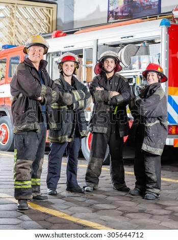 Full length portrait of confident firefighters standing arms crossed at fire station - stock photo