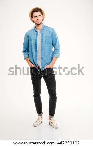 Full length portrait of confident handsome young man in blue shirt and hat over white background - stock photo