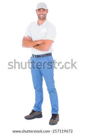 Full length portrait of confident handyman standing arms crossed on white background - stock photo