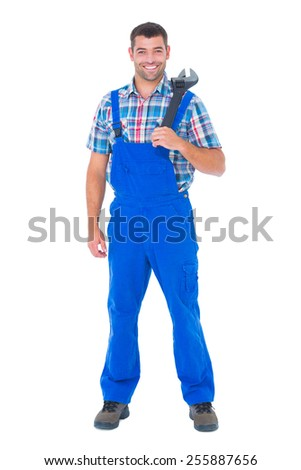 Full length portrait of confident male repairman holding adjustable wrench on white background - stock photo