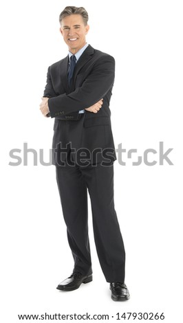 Full length portrait of confident mature businessman standing arms crossed isolated over white background - stock photo