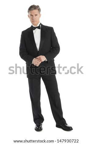 Full length portrait of confident mature man wearing tuxedo isolated over white background