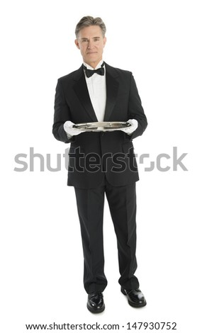 Full length portrait of confident mature waiter with serving tray standing against white background