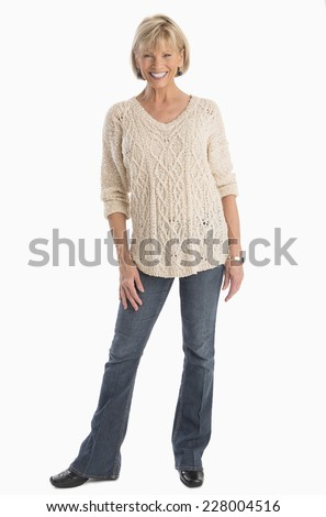 Full length portrait of confident mature woman in casuals standing over white background - stock photo