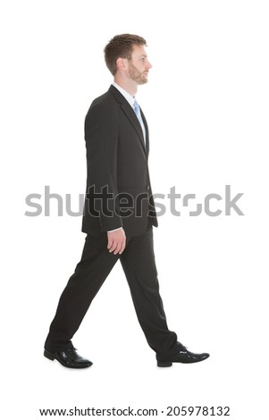 Full length portrait of confident mid adult businessman walking over white background - stock photo